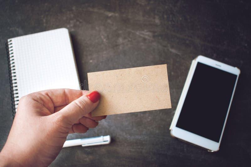 Visitenkartemodell Frauen übergeben das Halten der leeren PapierVisitenkarte auf defocused Smartphone- und Notizbuchhintergrund lizenzfreie stockfotos