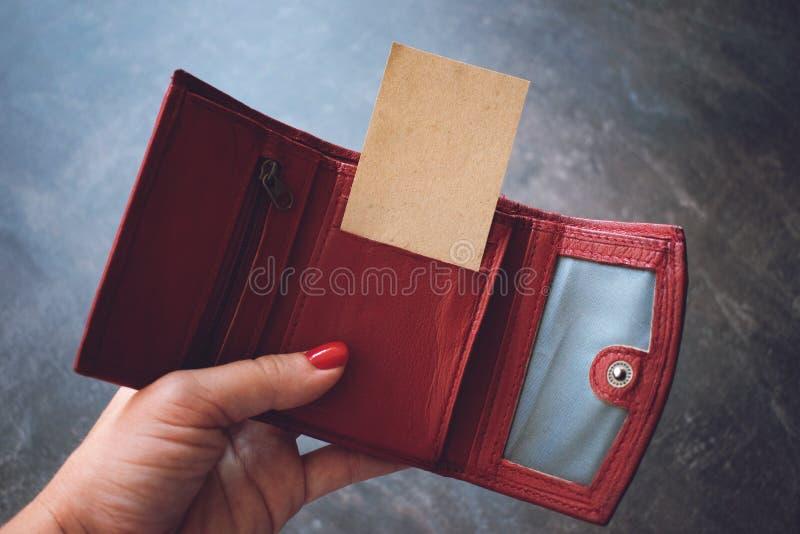 Visitenkartemodell Frauen übergeben das Halten der leeren PapierVisitenkarte in der roten ledernen Geldbörse stockfotos