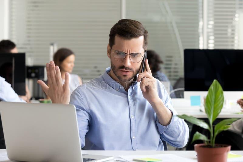 Visiteur fâché d'homme d'affaires parlant au téléphone contestant au-dessus du calcul photographie stock libre de droits