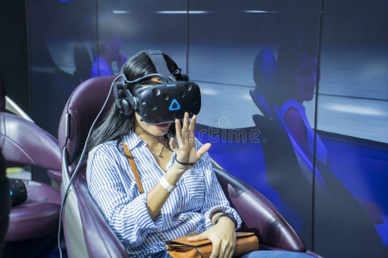 Visiteur féminin essayant un simulateur moteur à GIIAS image libre de droits