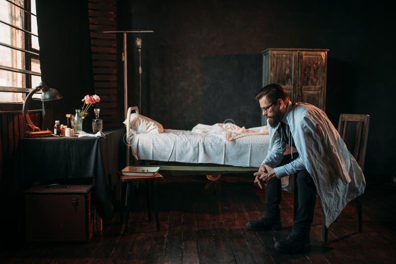 Visiteur masculin contre le lit d'hôpital vide image libre de droits