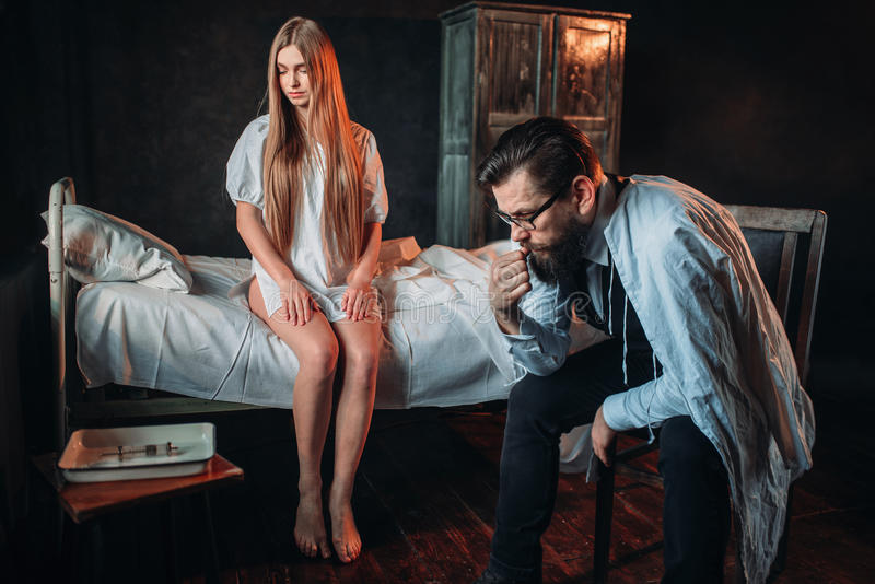 Visiteur s'asseyant contre la femme malade dans le lit d'hôpital photographie stock