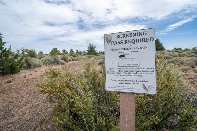Visiteurs d'avertissement de signe pour obtenir un passage examinant avant de présenter des cavernes en Lava Beds National image libre de droits