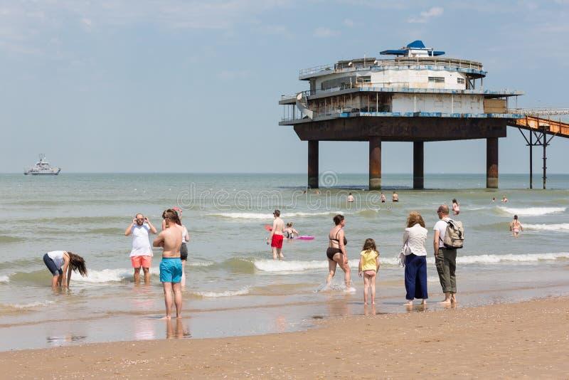Visiteurs de bord de la mer à la plage néerlandaise près du pilier de Scheveningen image stock