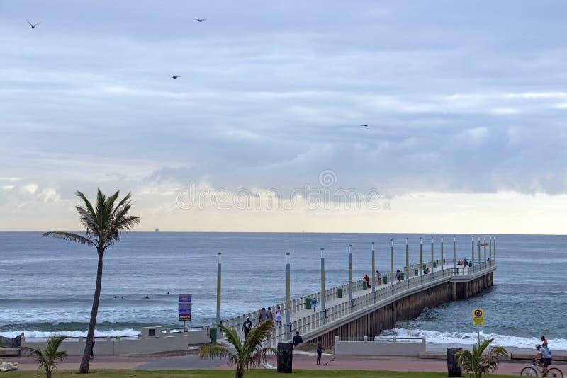Visiteurs de début de la matinée sur du front de mer et Pier Against Skyline photographie stock libre de droits