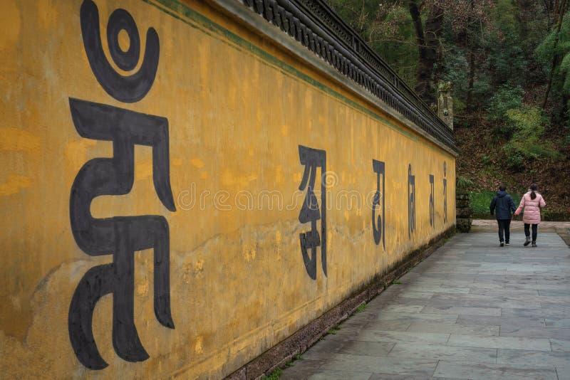 Visiteurs du complexe de temple marchant après un long mur avec photos stock