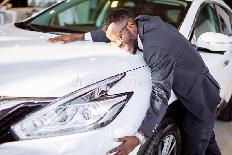 Handsome black man is hugging his new car and smiling. Visiting car dealership. Handsome black man is hugging his new car and smiling royalty free stock photo