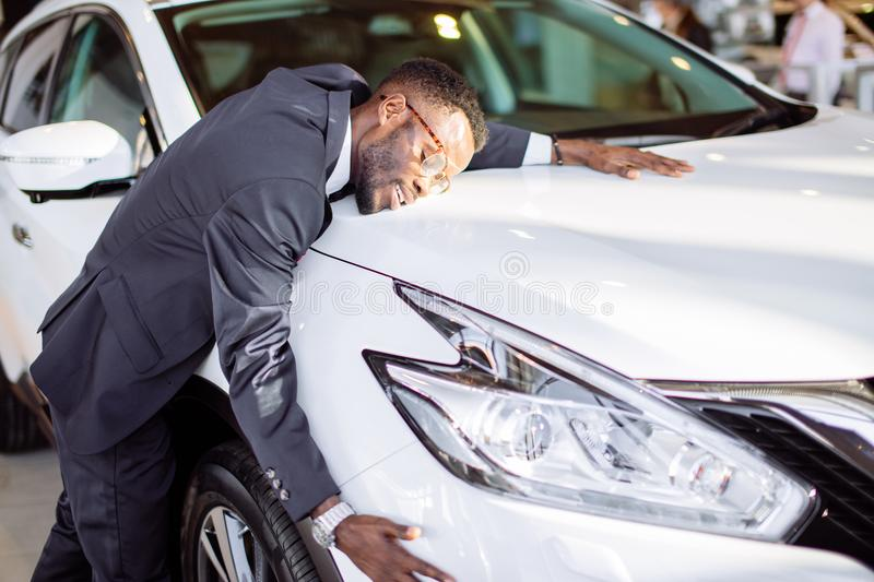 Handsome black man is hugging his new car and smiling. Visiting car dealership. Handsome black man is hugging his new car and smiling stock photo