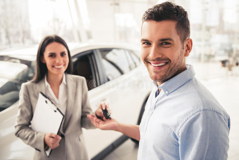 Visiting car dealership. Handsome men and beautiful sales manager are holding car key, looking at camera and smiling royalty free stock image