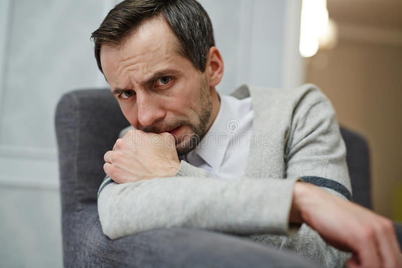 Visiting counselor. Uncertain man looking at camera during session stock images
