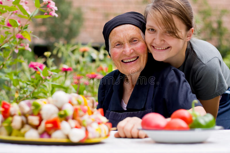 Visiting an elderly woman. A young woman - grandchild or carer - next to an old woman at the table, with fresh food in front of them royalty free stock image