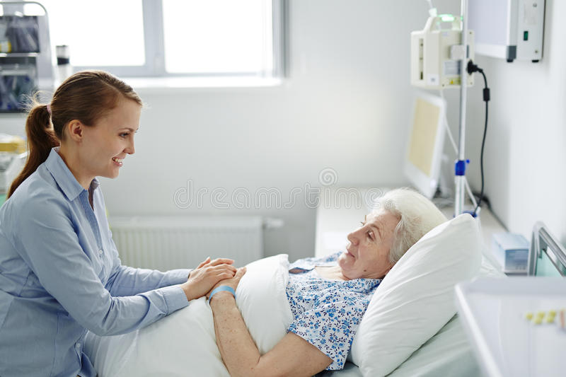 Visiting grandmother in hospital. Young girl visiting her sick grandmother in hospital royalty free stock photography