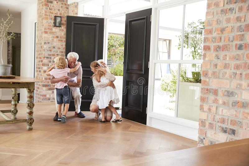 Visiting grandparents bend and kneel to hug grandchildren royalty free stock photography