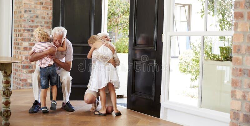 Visiting grandparents bend and kneel to hug grandchildren royalty free stock photo