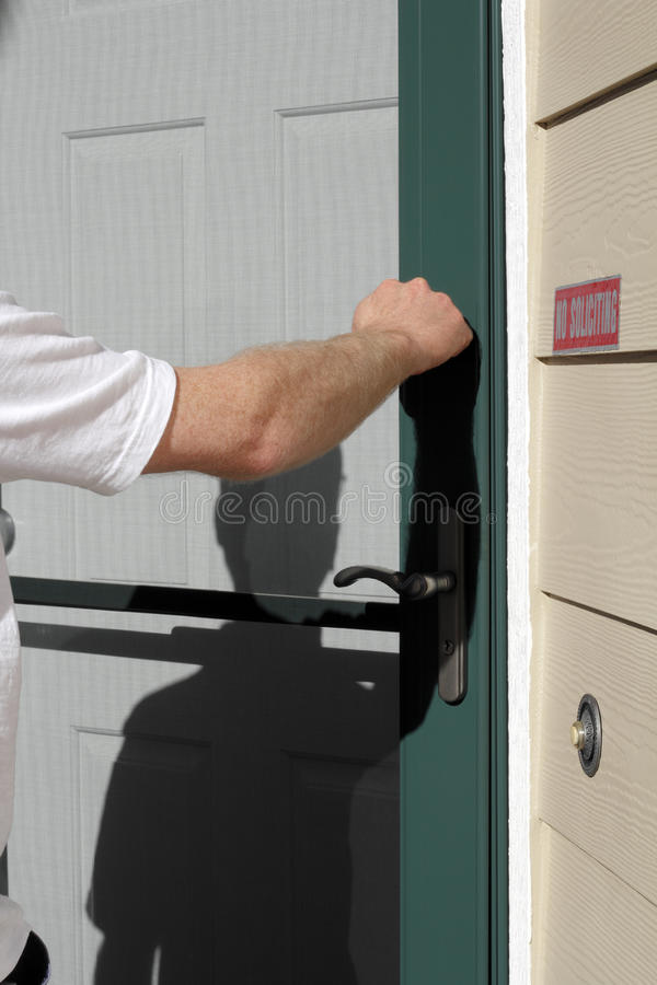 Visiting Time. Male knocking on a residential front door during the day royalty free stock image