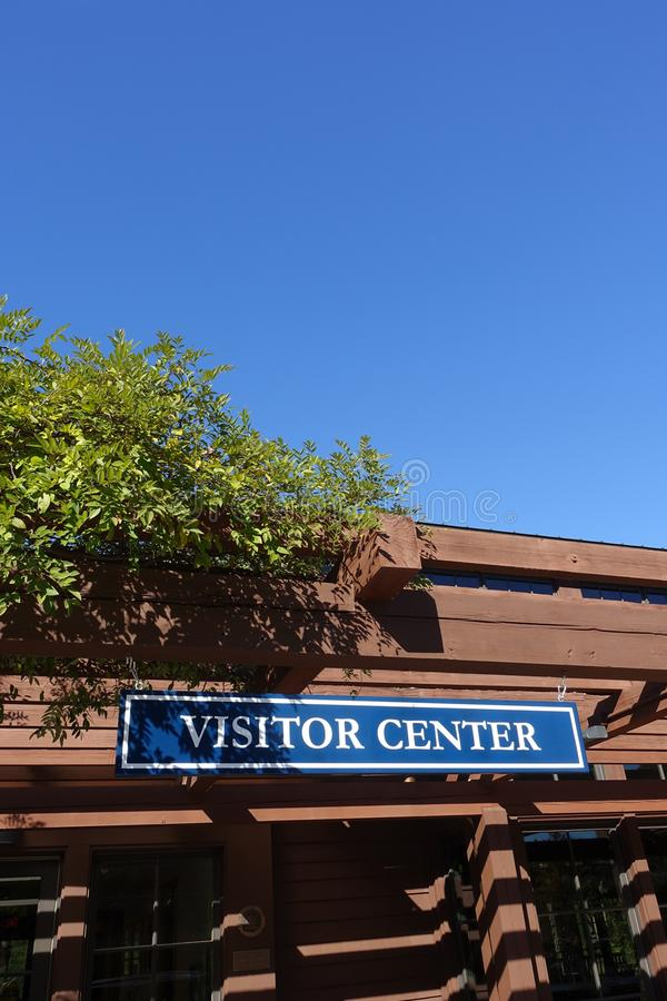 Visitor Center Sign with Blue Sky Background. Visitor center sign on the front of a building with blue sky background stock images