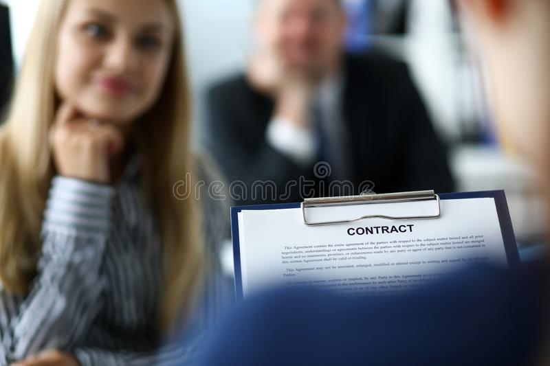Visitor examining contract application form clipped to pad. With corporate managers in background waiting for answer close-up royalty free stock photo