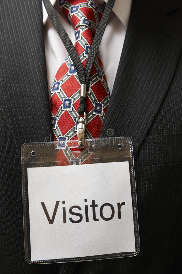 Visitor tag. Businessman wearing a visitor identification badge around his neck royalty free stock images