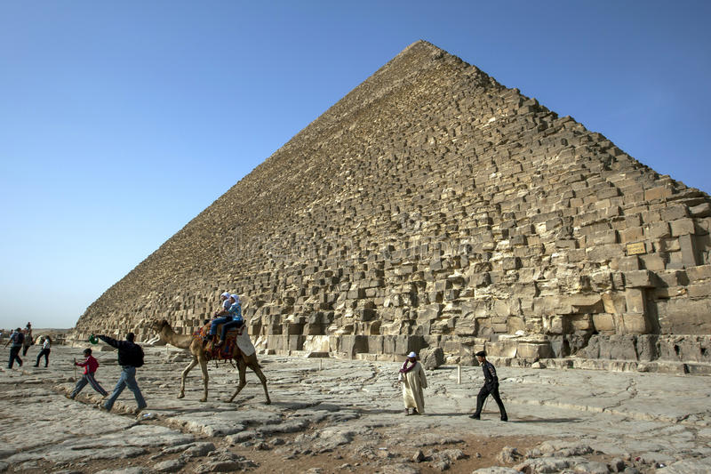 Visitors aboard a camel ride past the Great Pyramid of Khufu in Giza in Cairo, Egypt. It originally stood 146 metres high when it was completed around 2570 BC royalty free stock images