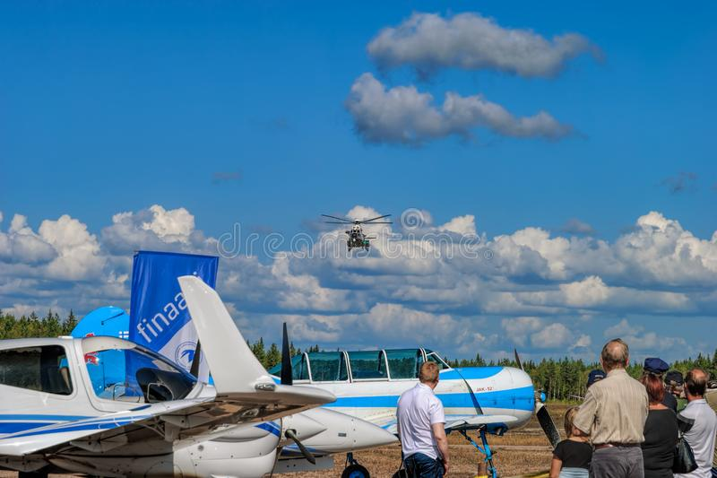 Visitors at an airshow watch at arrival of Airbus Helicopters H215 Super Puma heavy-lift utility aircraft OH-HVP by Finland`s. KOTKA, FINLAND - Aug 10, 2019 stock images