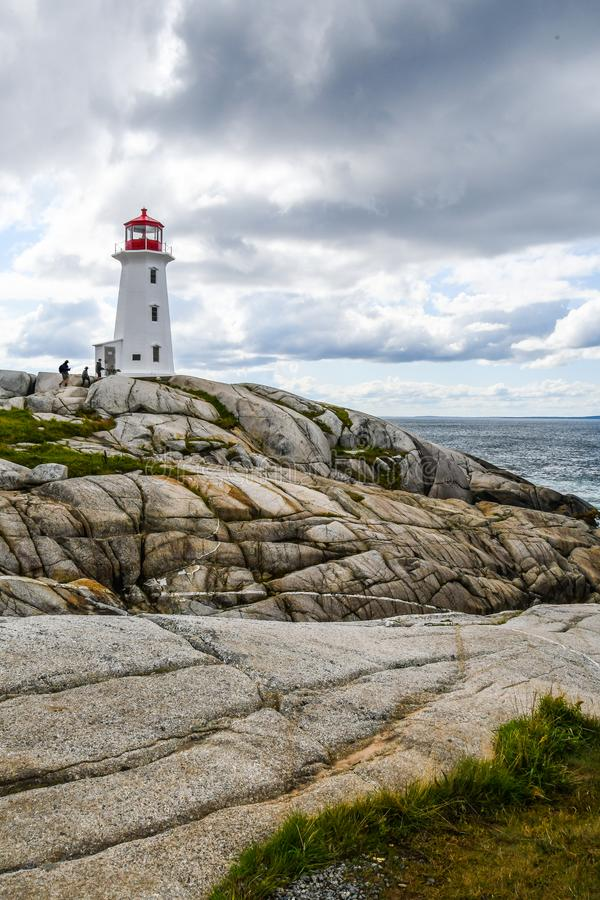 Visitors Climbing to the Peggy`s Cove Lighthouse in Nova Scotia stock photo