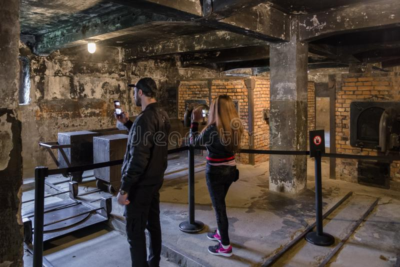 Visitors in the crematorium at Auschwitz I, Poland. OSWIECIM, POLAND - MAY 6: Visitors in the crematorium at concentration camp in Auschwitz on May 6, 2019 in royalty free stock photo