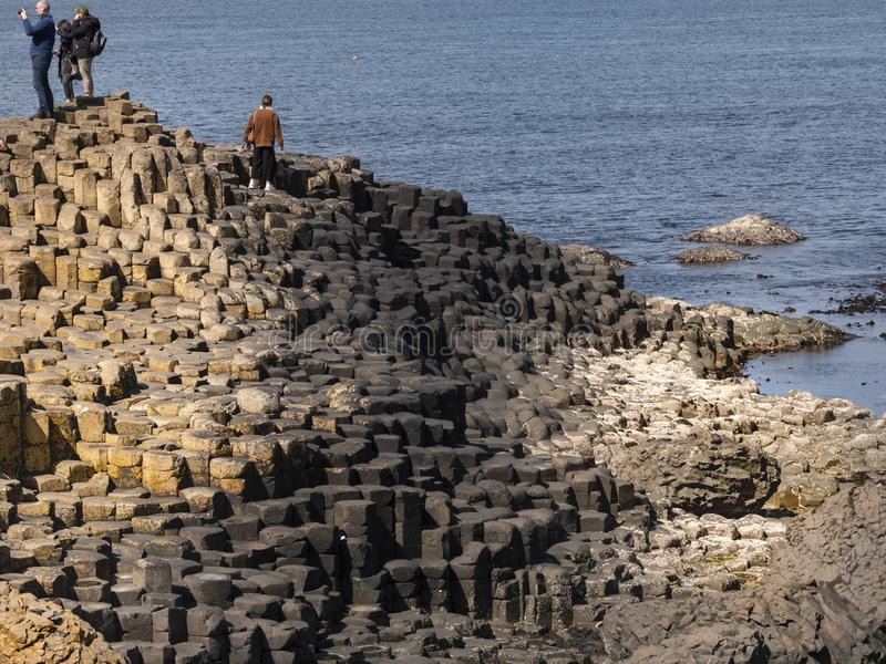 Visitors at Giants Causeway in Northern Ireland - BUSHMILLS. NORTHERN IRELAND - MAY 12, 2019. Visitors at Giants Causeway in Northern Ireland - BUSHMILLS. UNITED stock photo