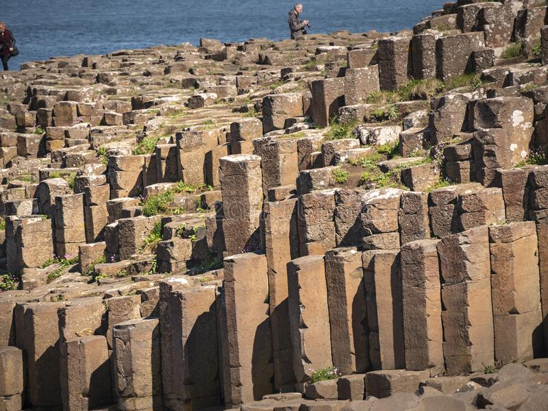 Visitors at Giants Causeway in Northern Ireland - BUSHMILLS. NORTHERN IRELAND - MAY 12, 2019. Visitors at Giants Causeway in Northern Ireland - BUSHMILLS. UNITED royalty free stock image