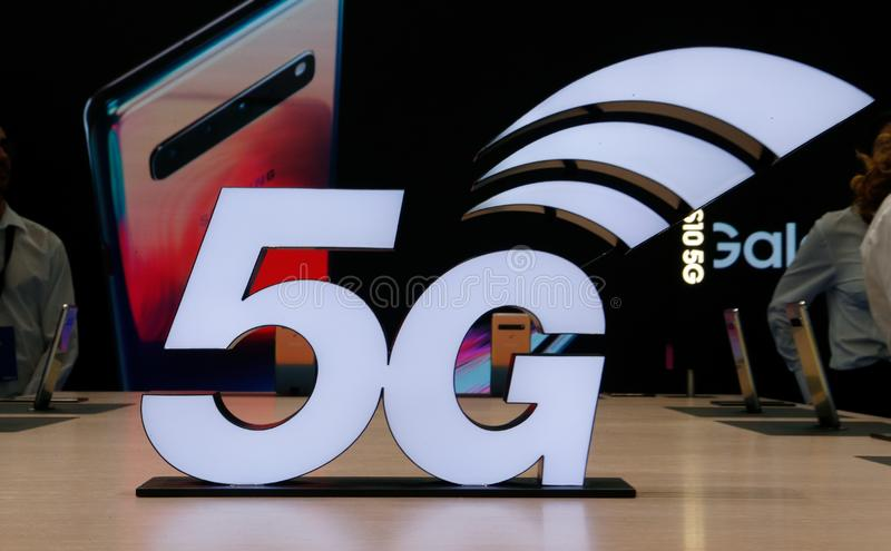 5G logo at MWC19 in Barcelona. Visitors handle and test mobile models next a giant 5G logo at the Mobile World Congress in Barcelona, Spain February 25 royalty free stock photo
