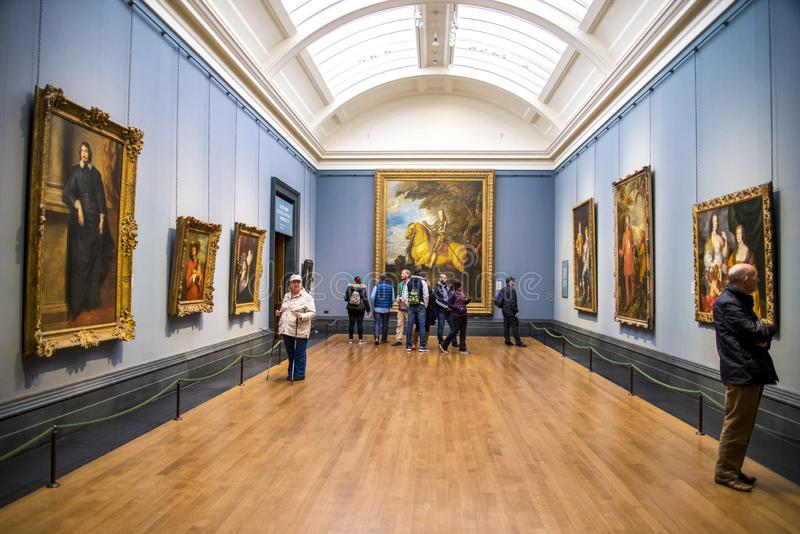 Visitors in one of the halls with hanging paintings in National Portrait Gallery, London, United Kingdom. October 2017 royalty free stock image