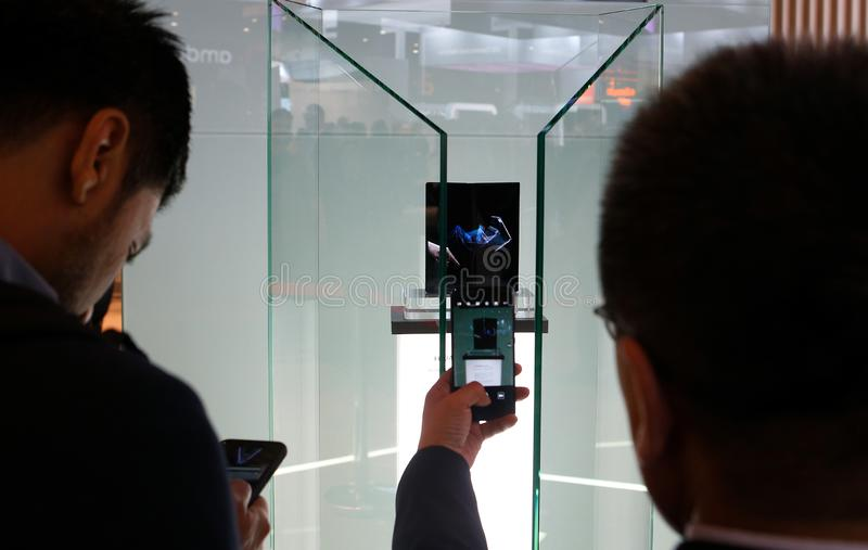 Visitors picturing Huawei foldable mobile on MWC 2019. Visitors take pictures of the new Huawei Mate X fold screen mobile inside their booth in the Mobile world stock photos