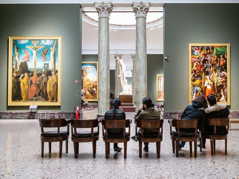 Visitors sit in hall in Pinacoteca di Brera. MILAN, ITALY - FEBRUARY 24, 2019: visitors sit in hall in Pinacoteca di Brera Brera Art Gallery in Milan. The Brera royalty free stock photography