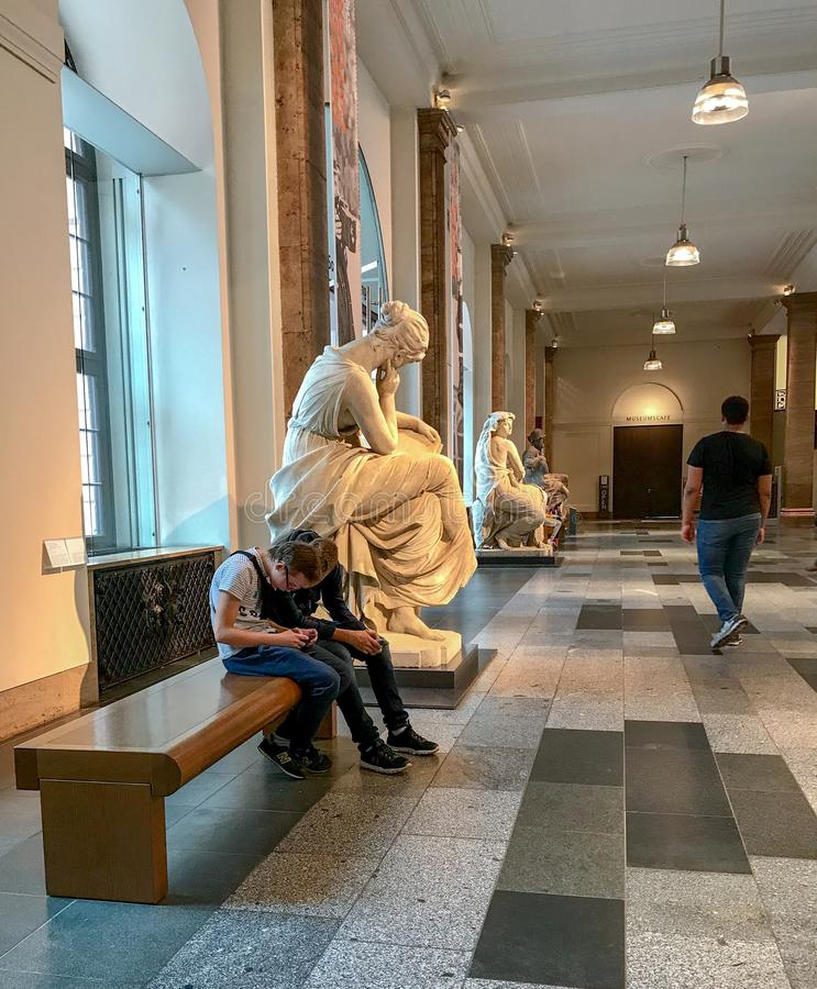 Visitors unconsciously mimic statue`s posture inside the Zeugha. September 2017: Visitors unconsciously mimic statue`s posture inside the Zeughaus museum, Berlin stock photography