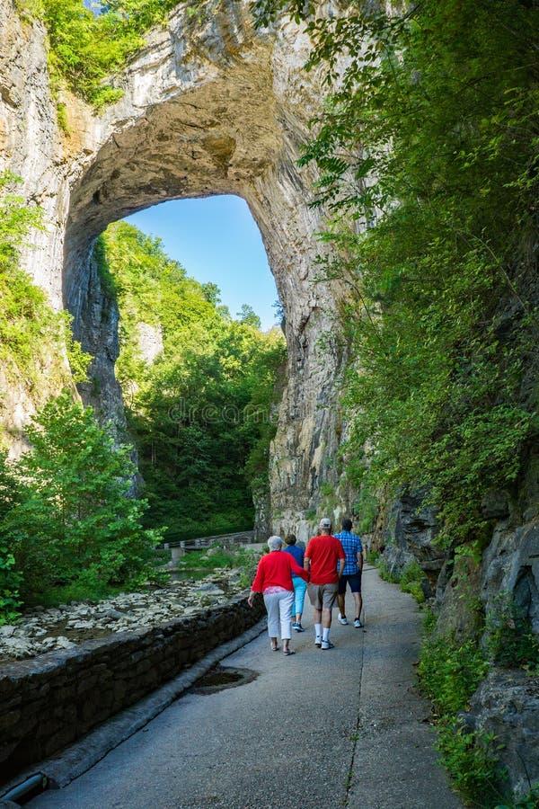Visitors under the Rock Arch at Natural Bridge State Park, Virginia, USA. Natural Bridge State Park, Rockbridge County, VA – August 24th: Visitors enjoying a royalty free stock image