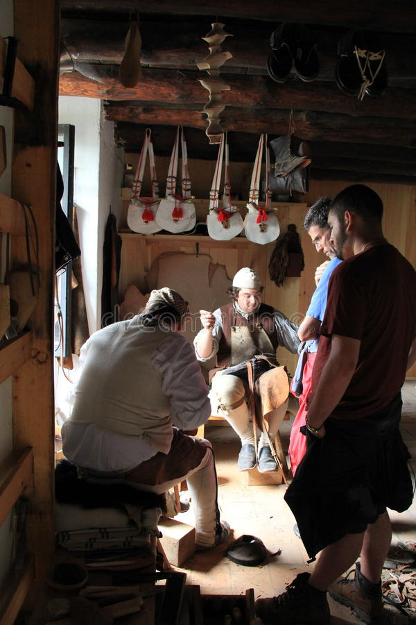 Visitors watching tailors sew leather garments,Fort Ticonderoga,New York,2014. Visitors looking on as men dressed in period clothes reenact the life of a tailor stock images