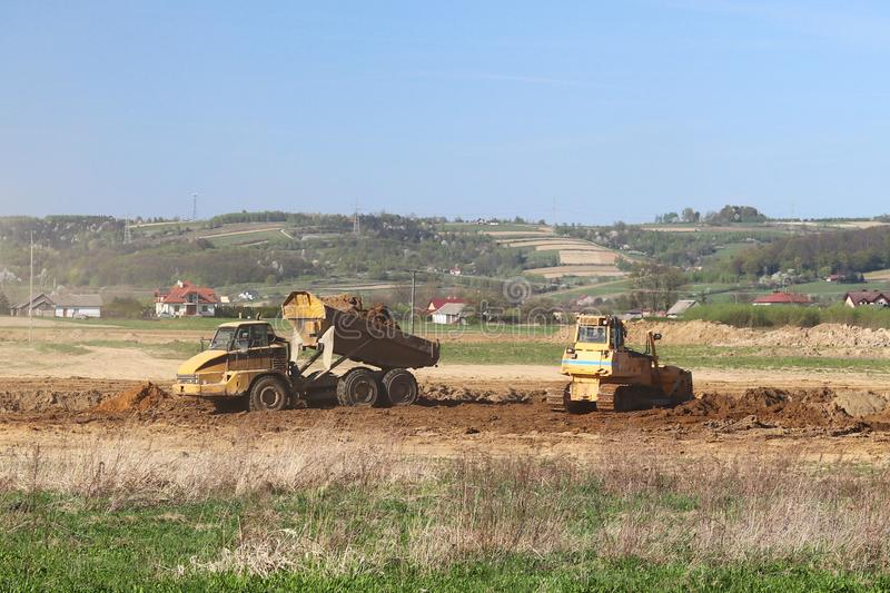 Vislock river, Poland - may 2, 2018:A dump truck is loaded with soil. Land works in the quarry of river gravel. Extraction of natu. Ral resources. A bulldozer royalty free stock photography