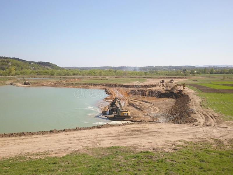 Vislock river, Poland - may 2, 2018:The excavator loads the dump truck with soil.Land works in the quarry of river gravel. Extract stock image