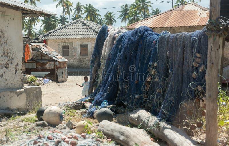 Visnetten die op houten dwarsligger in dorp hangen stock foto's
