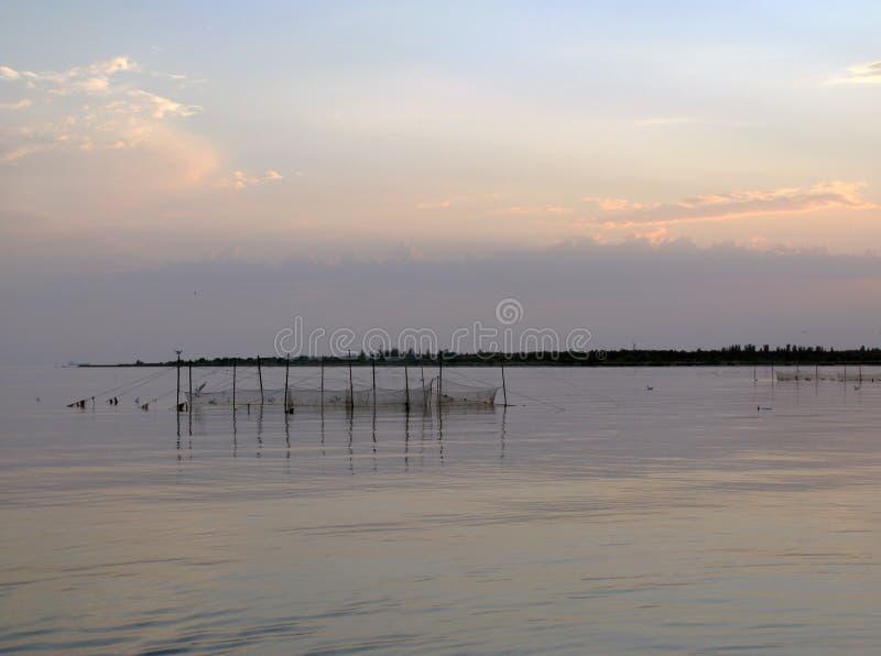 Visnetten in kalme overzees bij zonsondergang royalty-vrije stock foto