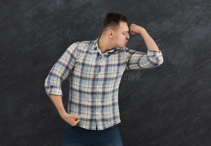 Visning för ung man och kyssa hans biceps royaltyfri bild