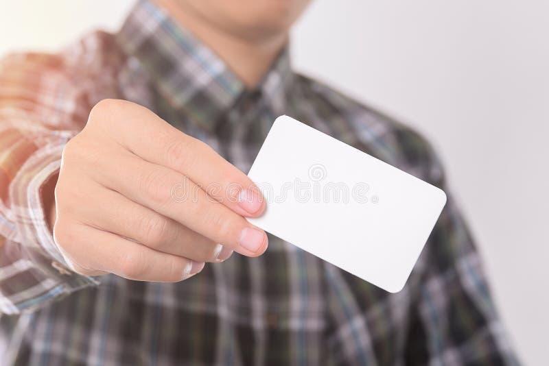 Visning för ung man som ger det tomma affärskortet från facket av hans skjorta för övre designTemplet för åtlöje royaltyfri bild