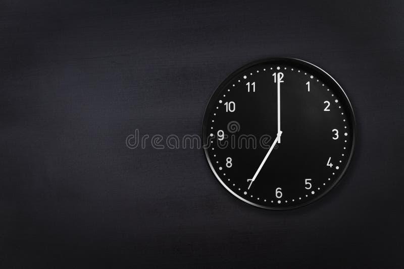 Visning för väggklocka sju klockan på svart svart tavlabakgrund Kontorsklocka som visar 7am eller 7pm på svart textur royaltyfri foto