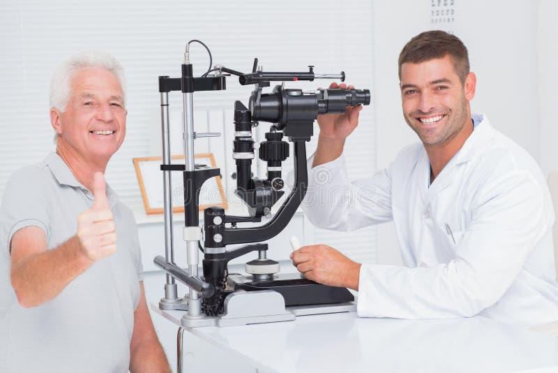 Visningen för hög man tummar upp, medan sitta med optiker arkivbilder