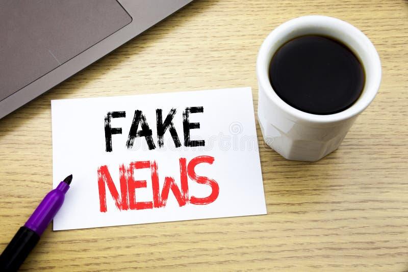 Visningen för handskriftmeddelandetext fejkar nyheterna Affärsidé för Hoax journalistik som är skriftlig på anteckningsbokboken p royaltyfri bild