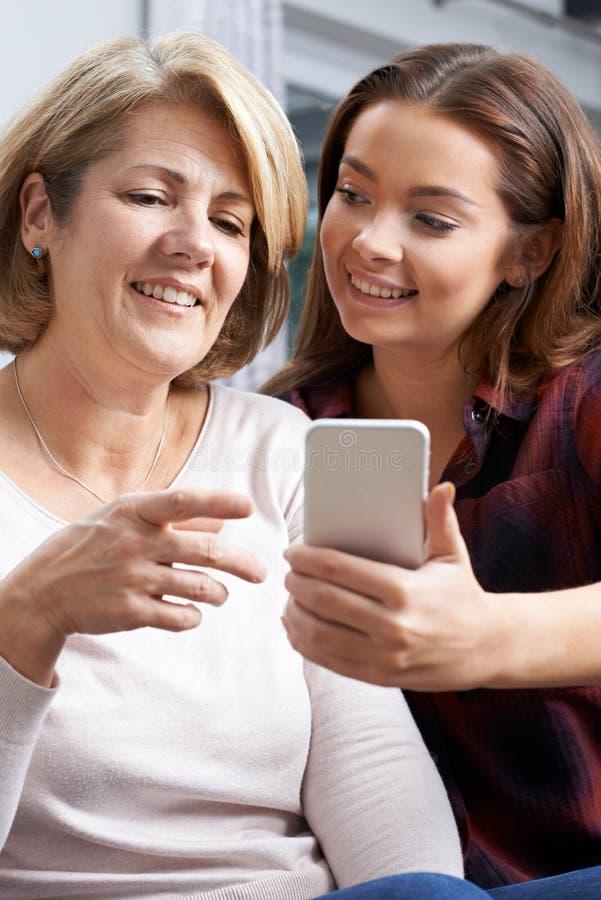 Visningmoder för tonårs- dotter hur man använder mobiltelefonen royaltyfria bilder