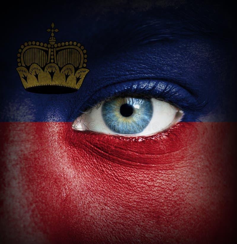 Viso umano dipinto con la bandiera del Liechtenstein fotografia stock libera da diritti