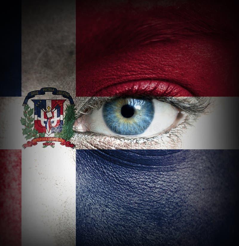 Viso umano dipinto con la bandiera della Repubblica dominicana fotografia stock libera da diritti