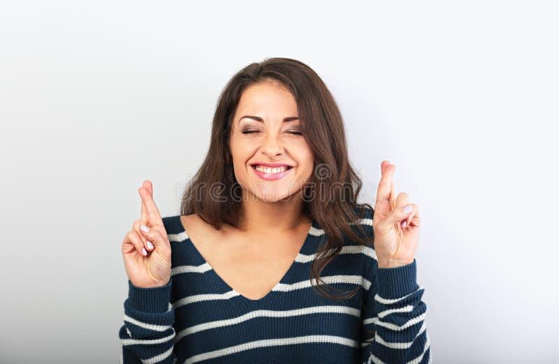 Vissage heureux vers le haut de la belle femme de yeux croisant ses doigts, espérant, demandant le souhait photos libres de droits