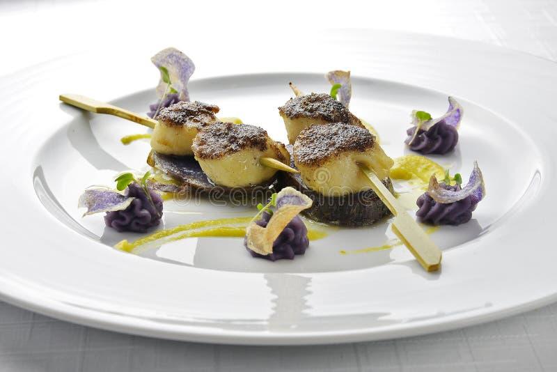Visschotelvleespen van Kammosselen Vastgeroest met zwarte Rijst en Purple stock foto