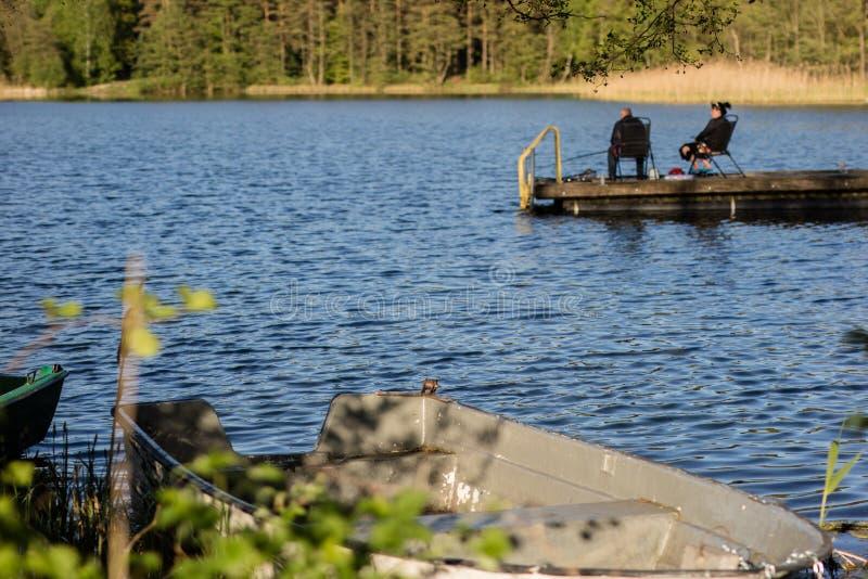 Vissen die bij een meer in Midden-Europa vissen Vissers die op vissen stock afbeelding